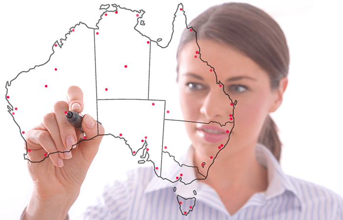 woman drawing network locations on an australian map with red pen